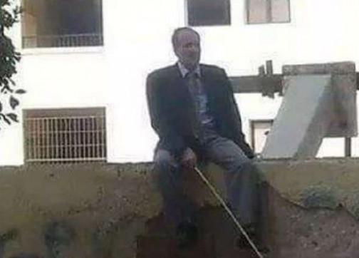 مدير مدرسة يجلس على السور بعصا لمنع التلاميذ من الهروب