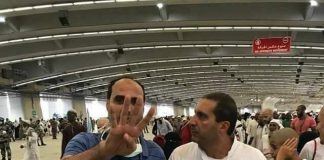صورة لعمرو خالد مصدوم رفقة أحد الحجاج وقد رفع شارة رابعة