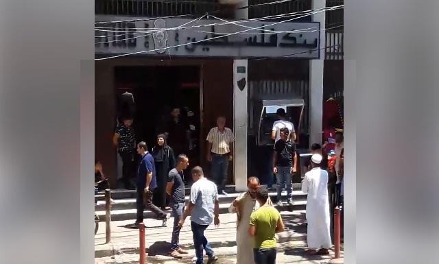 فيديو.. بمكبر صوت يقف أمام مدخل أحد البنوك ويحذر من التعامل بالربا