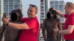 """صورة: بعنصرية واحتقار.. """"إسرائيلي"""" يتسلى بالتقاط صور مع مهاجر إفريقي وجده يستحم بشاطئ """"تل أبيب"""""""